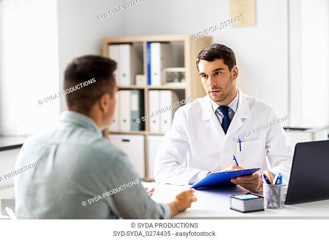 doctor with clipboard and male patient at hospital