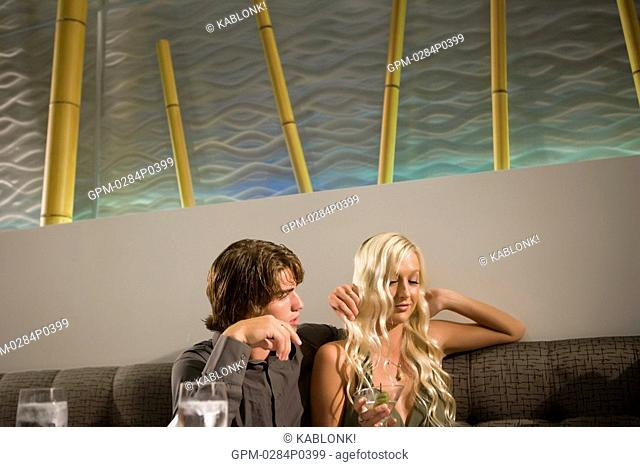 Portrait of young couple sitting in booth at upscale restaurant
