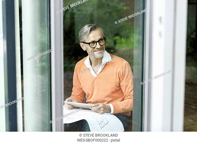 Smiling man with construction plan and tablet