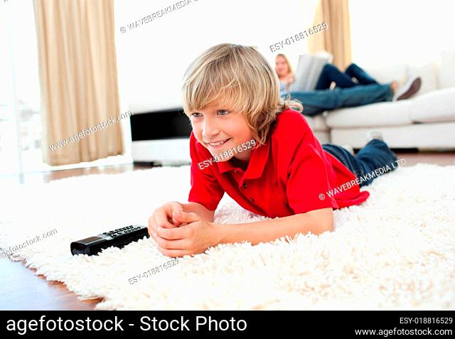 Concentrated boy watching TV lying on the floor