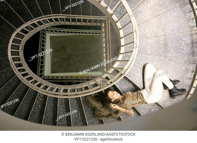 woman laying on stairs in staircase, alone, in Munich, Germany