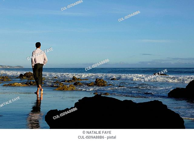 Businessman walking on El Matador beach, California, USA