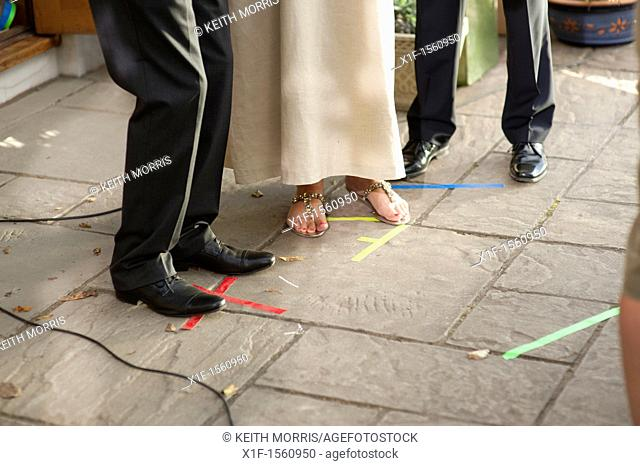 Actors standing on their tape marks working on the location recording of a television drama series, UK