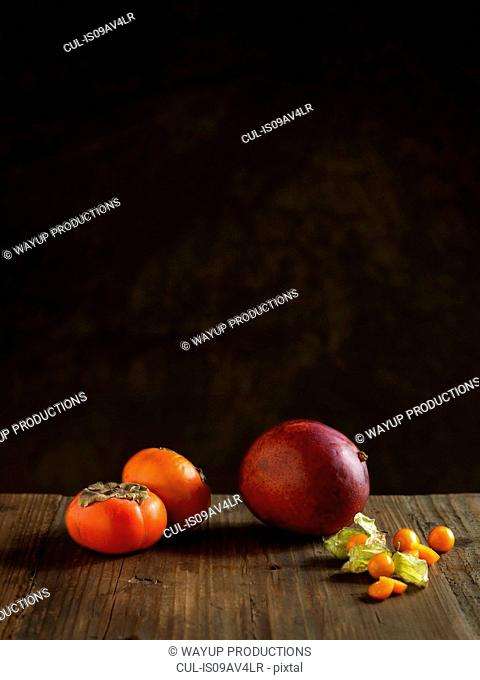 Whole mango and persimmons on wood table against dark background