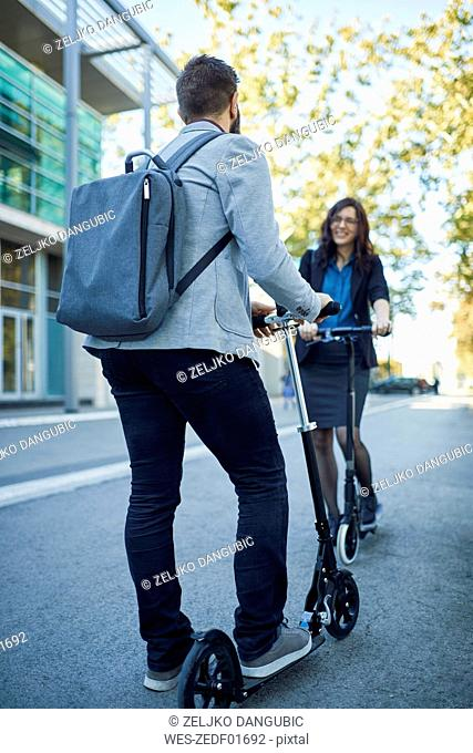 Businessman and businesswoman meeting with scooters