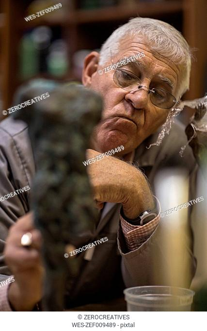 Senior man inspecting bronze cast