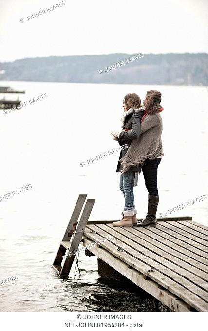 Mother and teenage daughter looking at water
