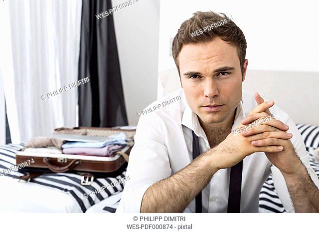 Businessman sitting on bed with clasped hands