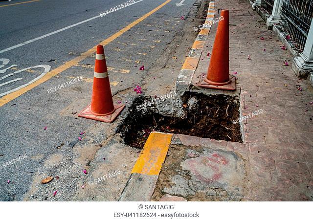 Plastic orange cone at the pothole on asphalt road