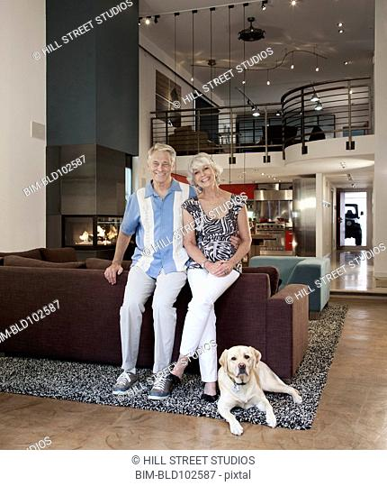 Smiling Caucasian couple sitting together in living room