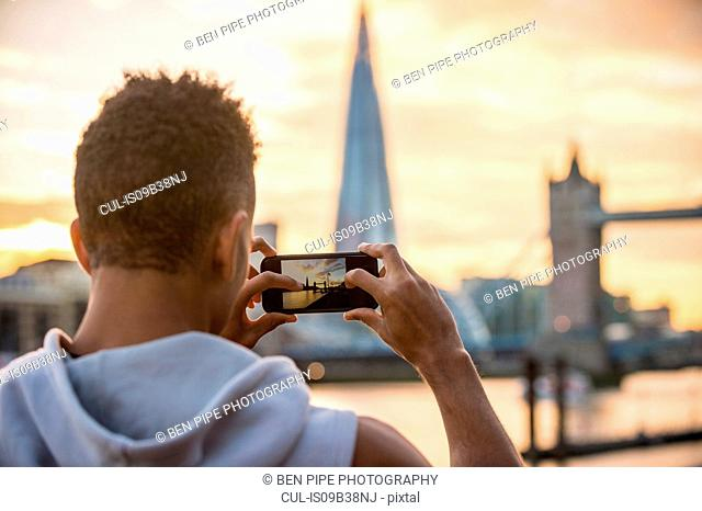 Man by riverside taking photograph of Tower Bridge and The Shard, Wapping, London, UK