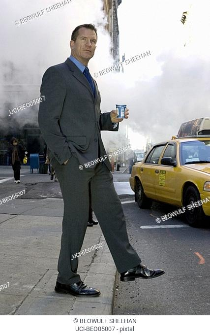 Businessman stepping off curb onto busy street