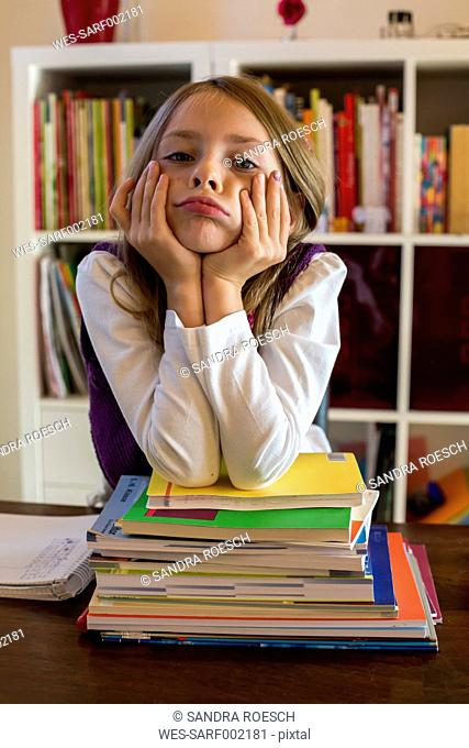 Portrait of unhappy girl leaning on stack of school books