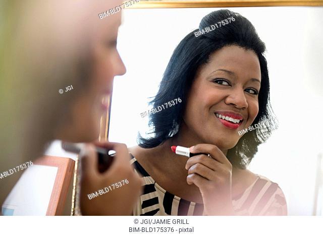 Black woman applying lipstick in mirror