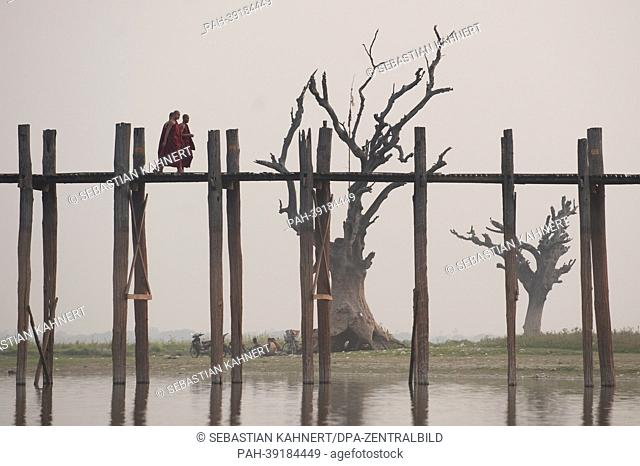 Three Buddhist monks walk across the U Bein Bridge on the Taungthaman Lake in Amarapura, Myanmar, 02 April 2013. Photo: Sebastian Kahnert | usage worldwide
