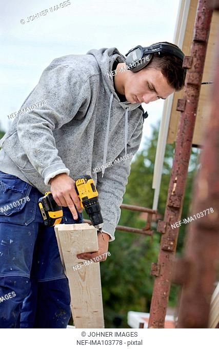 Young man with electric drill