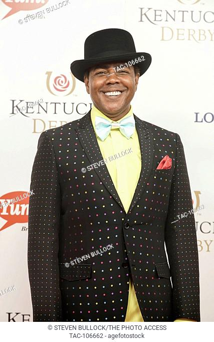 Actor Kirk KelleyKahn with black Bola hat, sparkling jacket, yellow shirt pastel blue tie smiling on the Red Carpet