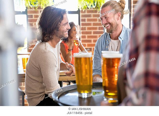 Waitress Serving Two Male Friends Meeting For Drink In Bar