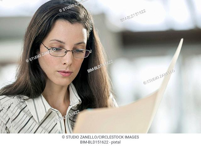 Businesswoman reading folder in office