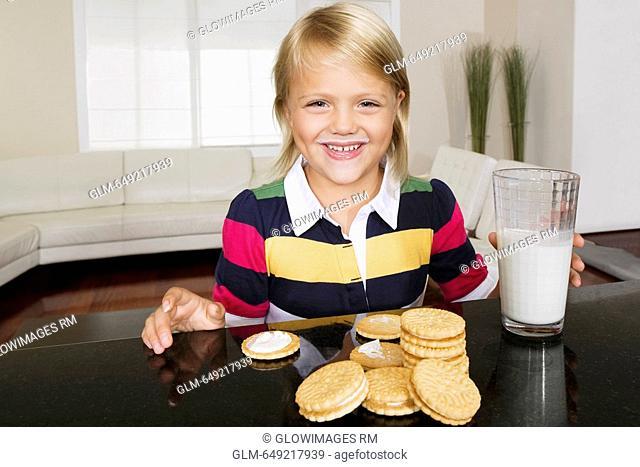 Girl having cookies and milk