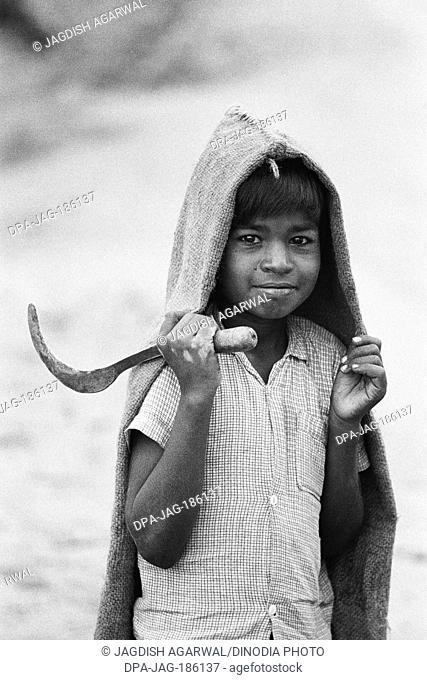 Boy with sickle and jute raincoat Mysore Karnataka India Asia 1977