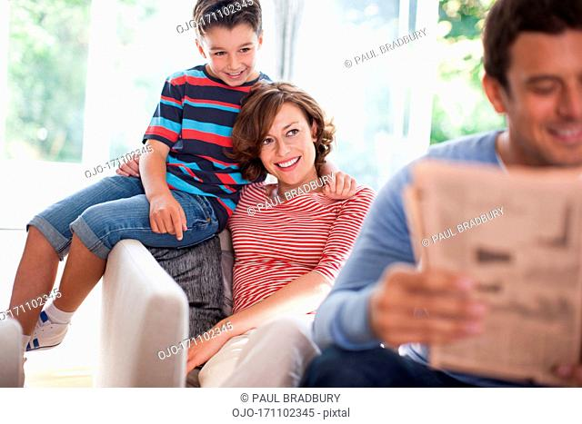 Father reading newspaper with mother and son in background
