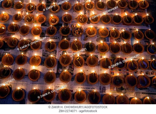 Lamps burn as a tribute to the goddess Durga in worship at Shakharibaza temple in Dhaka, Bangladesh