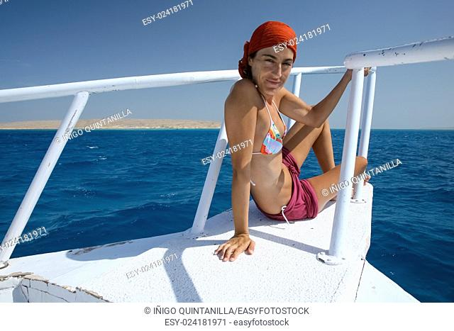 woman scarf and bikini sitting on white bow of boat or yacht looking, in Egyptian Red Sea, blue ocean water next to Sharm al Sheij and Hurghada, Egypt, Africa