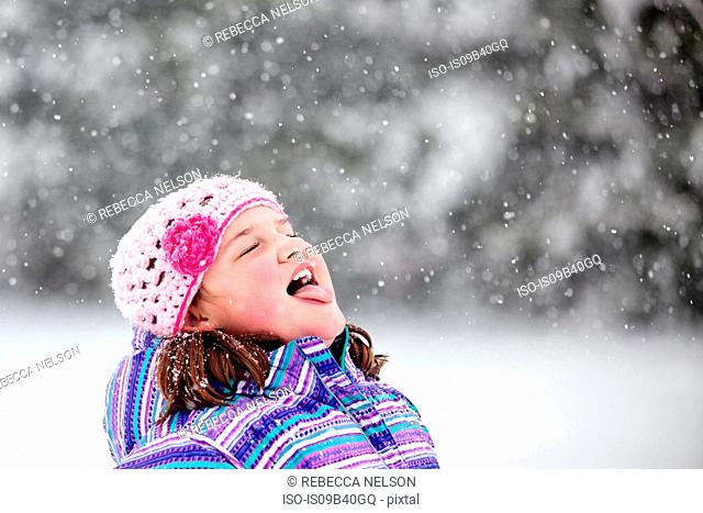 Girl catching snowflake on her tongue