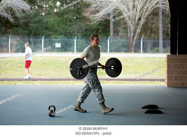 Female soldier carrying barbell at military air force base