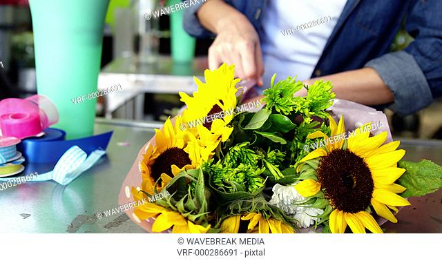Female florist preparing flower bouquet