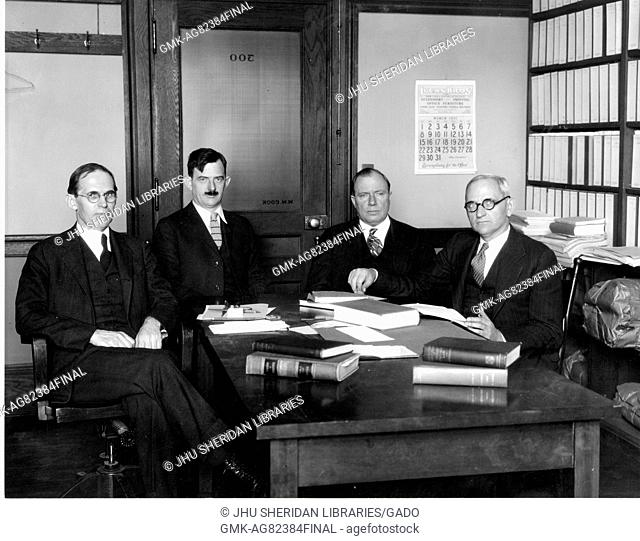 Group photograph of Johns Hopkins Law professors Walter Cook, Hessel Yntema, Leon Marshall, and Herman Oliphant sitting around a table with open books inside...