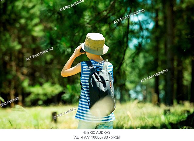Boy looking through binoculars in woods
