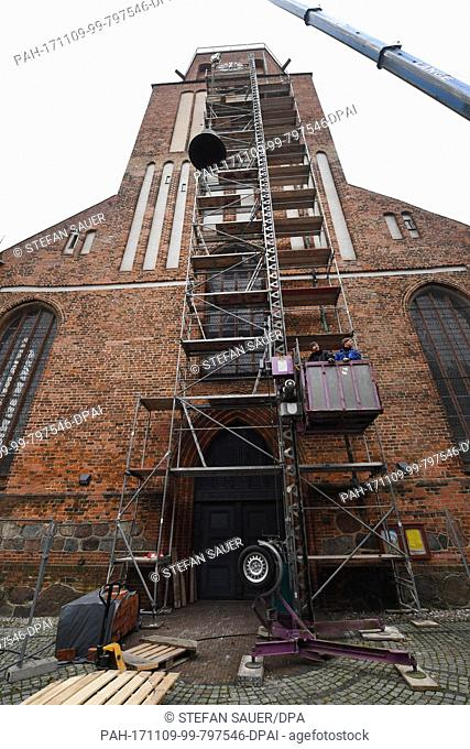 A bell technician transports a 1.7 ton heavy bronze bell into the tower of the St. Petri church with the help of a crane in Wolgast, Germany, 09 November 2017