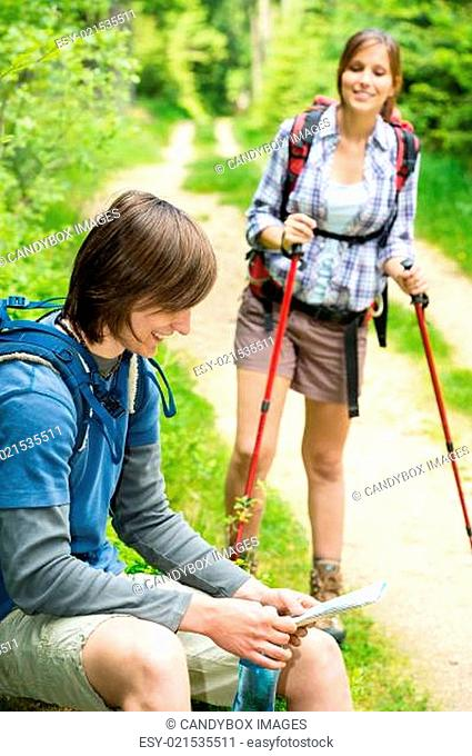 Male hiker watching map waiting for girl