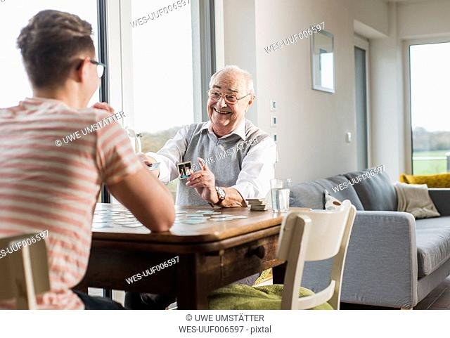 Portrait of happy senior man playing memory with his grandson