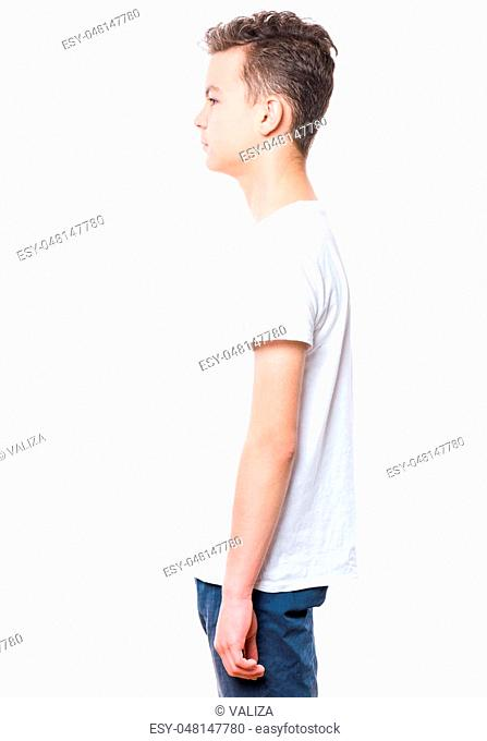 White t-shirt on teen boy. Handsome caucasian child - profile, isolated on a white background. Concept of childhood and fashion or advertisement design