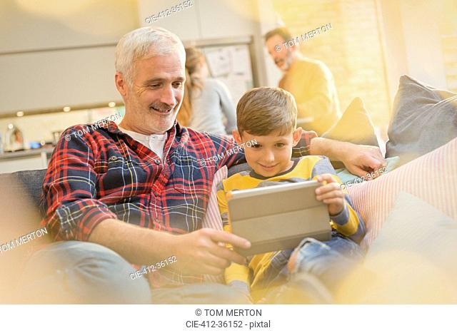 Father and son bonding, using digital tablet on sofa