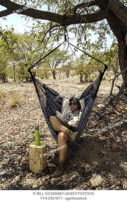 Man relaxing in Hammock - Huab Under Canvas, Damaraland, Namibia, Africa