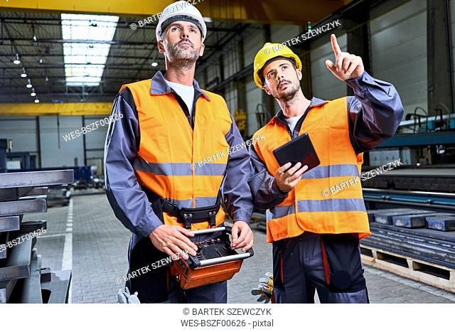 Two men in factory talking and operating machinery with remote console