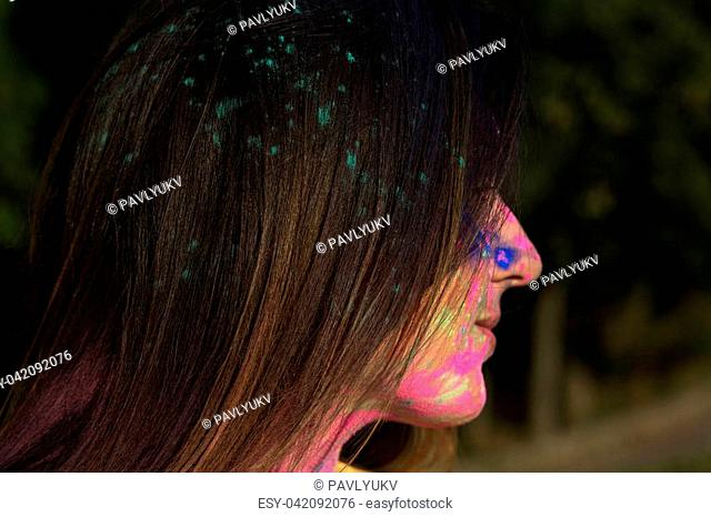 Closeup portrait of attractive young brunette model posing on the Holi festival