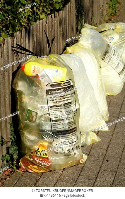 Yellow bags with plastic waste, hanging on garden fence, waste separation, Lower Saxony, Germany