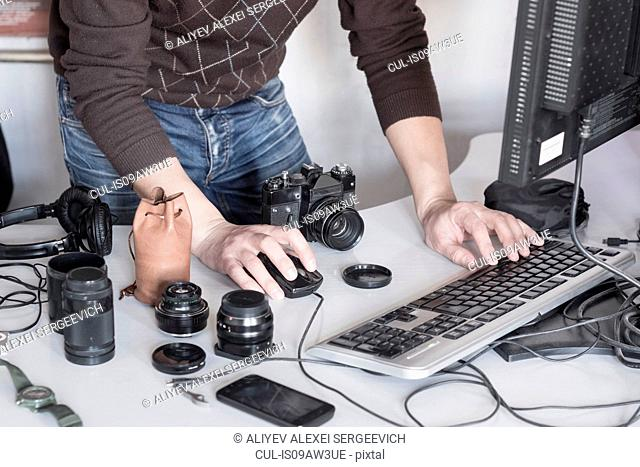 Photographer uploading photos from camera into computer in studio