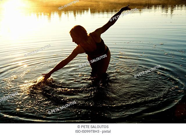 Woman touching water in lake