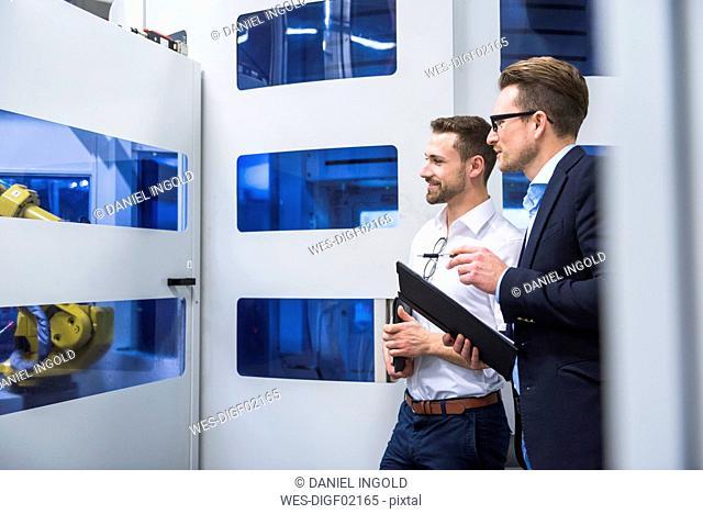 Two men talking in factory shop floor looking at machine