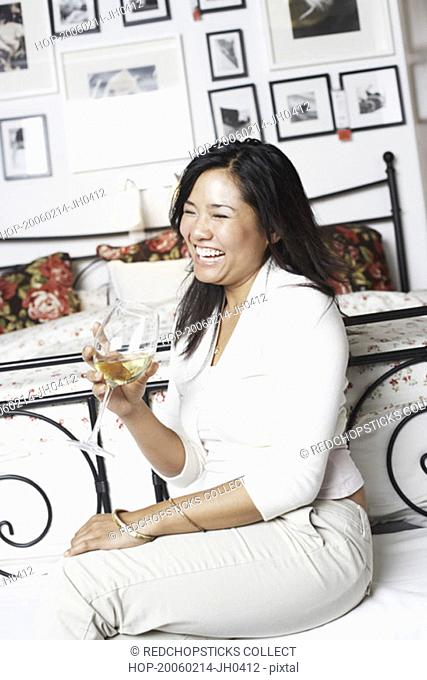 Side profile of a young woman holding a glass of wine smiling