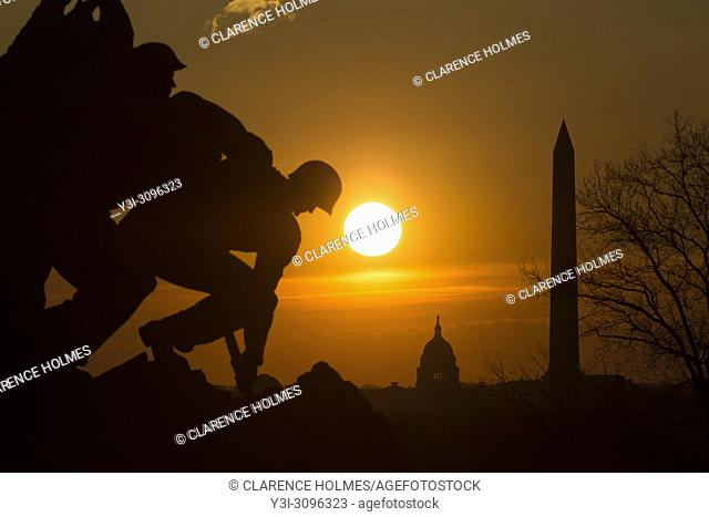The US Marine Corps War Memorial is silhouetted against an orange sky at sunrise, with Washington landmarks in the background in Arlington, Virginia