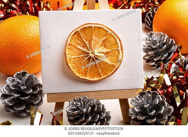 dried orange slice on a easel as a christmas motive, pine cones with white tips around