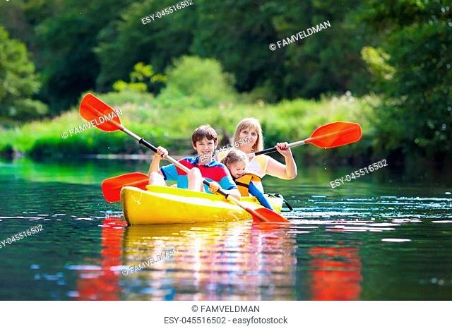 Child with paddle on kayak. Summer camp for kids. Kayaking and canoeing with family. Children on canoe. Little boy on kayak ride