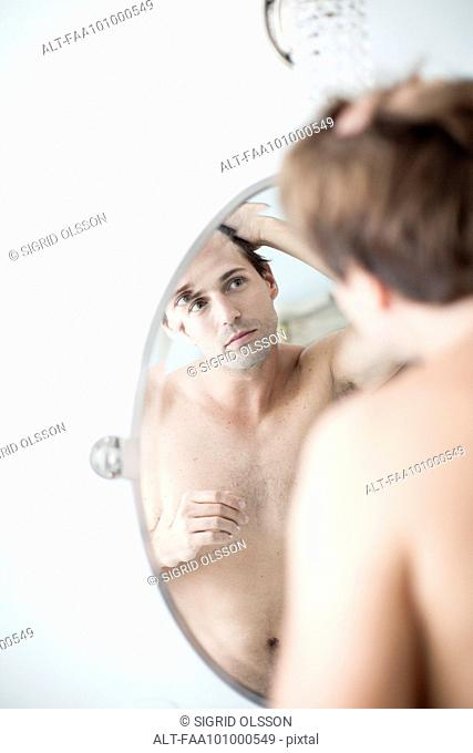 Man examining hairline in mirror